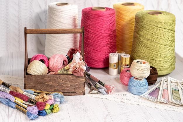 Нитки в барабанах. цветные шпульки для вышивки вязанием аксессуаров для хобби творчество. фон для сайта