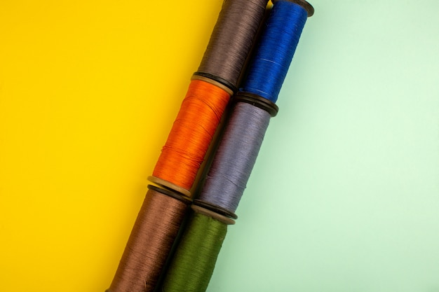 Нитки разноцветные для шитья на желто-зеленом полу