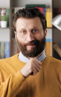 脅威。カメラを見て、彼の首に沿って脅迫指を実行しているオフィスやアパートの部屋で眼鏡をかけている自信のあるひげを生やした男。クローズアップビュー