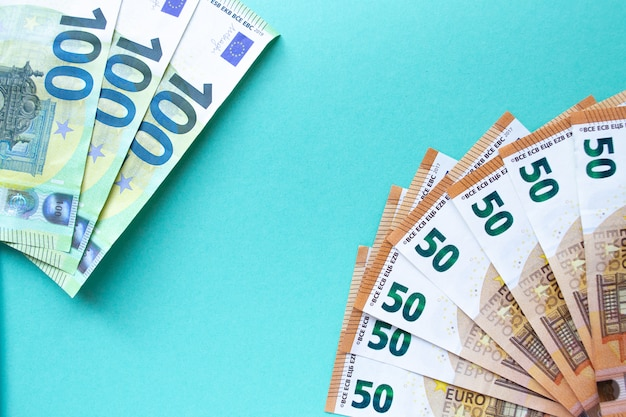 Three 100 euro banknotes on the left and 50 euros in lower right corner. on a blue background. the concept of money and finance. with place for text.