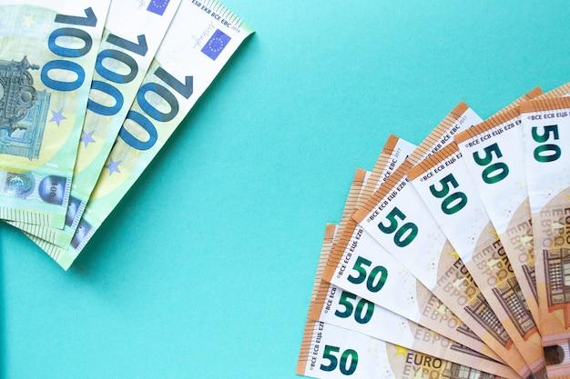 Три банкноты 100 евро слева и 50 евро в правом нижнем углу. на синем фоне. понятие денег и финансов. с местом для текста.
