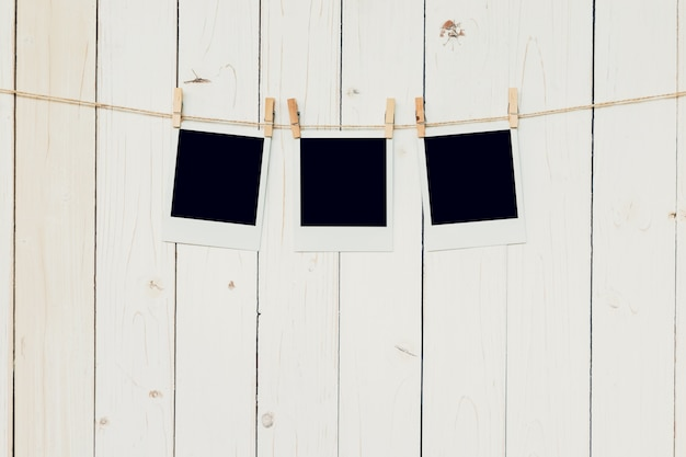 Three (3)blank photo frame hanging on white wood background with space.