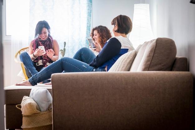 Три 3 девушки дома на досуге в помещении вместе время дружбы и отношений, используя смартфон, чтобы общаться с друзьями или проверять социальные сети в интернете