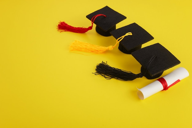Three academic hats with diploma on yellow background graduation theme