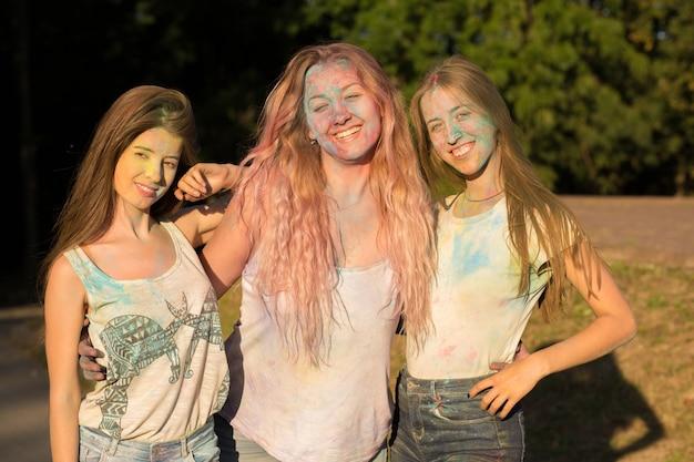 ホーリー祭を祝う3人の愛らしい金髪の女性の友人