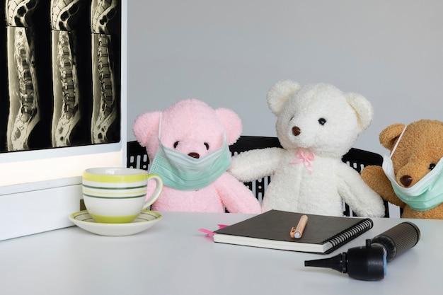 의료 회의실에서 안면 마스크를 쓴 사랑스러운 작은 봉제 장난감 곰 세 마리
