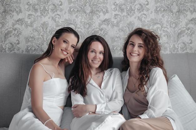 スタイリッシュでカジュアルな白い服を着た3人の大人の女性は、ベッドで時間を過ごし、甘くおしゃべりし、話をし、笑います。大人の友達が出会い、ホテルの部屋で余暇を過ごします。女性の友情の概念