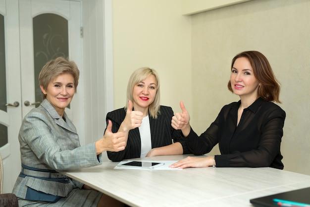 정장에 세 성인 여성이 손의 제스처와 함께 사무실에서 직장에서 태블릿과 함께 테이블에 앉아있다