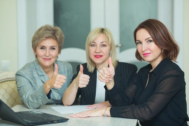 Три взрослых женщины в костюмах сидят за столом с ноутбуком за работой в офисе жестом рук