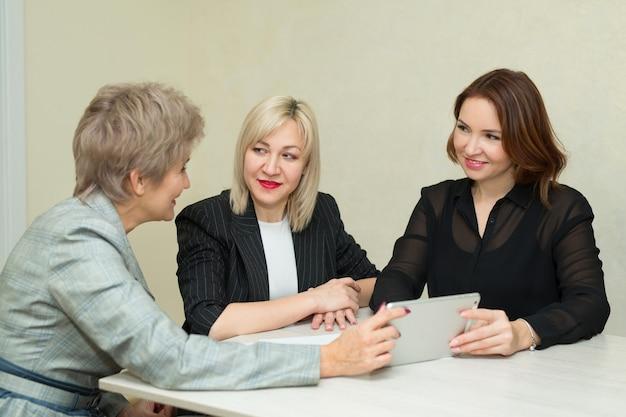 Три взрослых женщины в костюмах сидят за столом с ноутбуком за работой в офисе