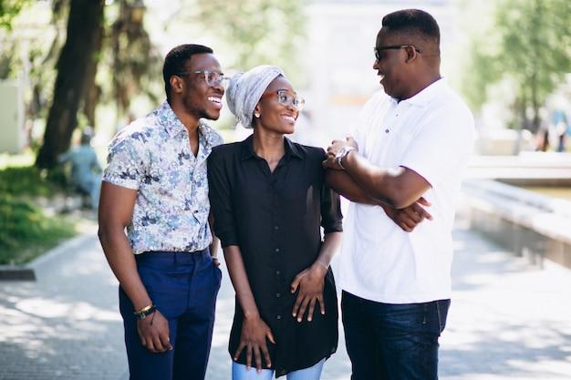 Three afican american people talking in the street