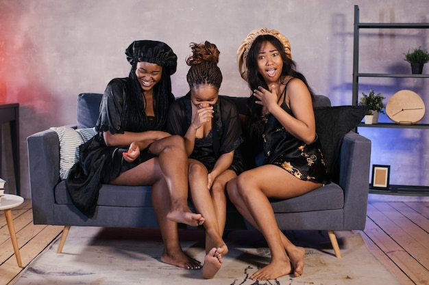 Три афро-американских девушки сидят на диване, смотрят телевизор и смеются