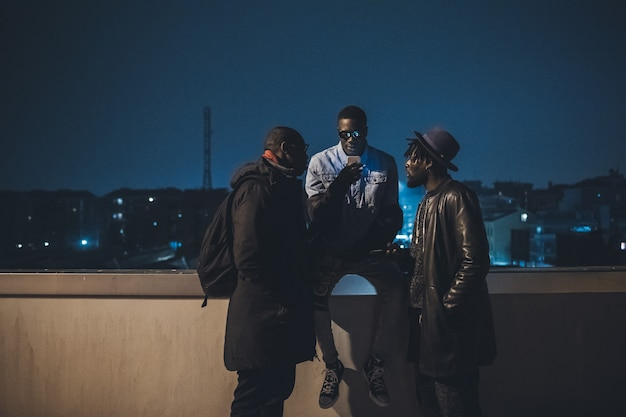 Three african friends sitting outdoor and looking the smartphone