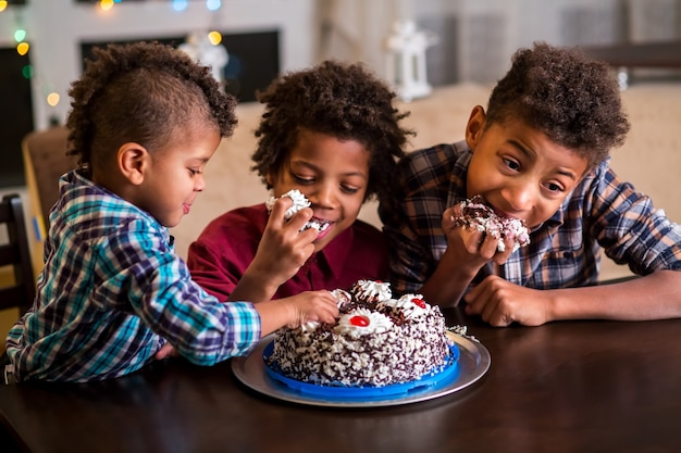ケーキを食べる3人のアフロの男の子。