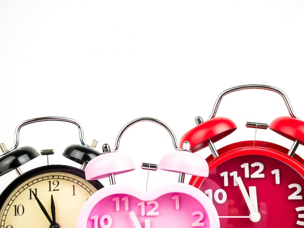 Three alarm clock, red, pink, black isolated on white background