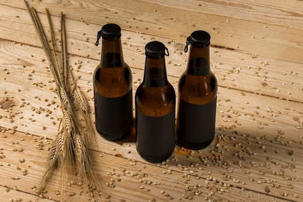 Three alcoholic bottles and ears of wheat on wooden surface