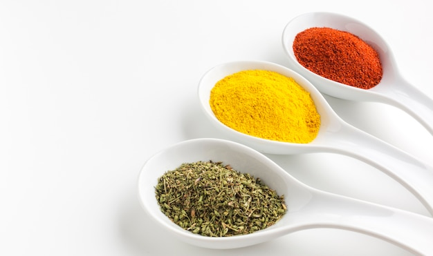 Three aligned spoons with spices powder
