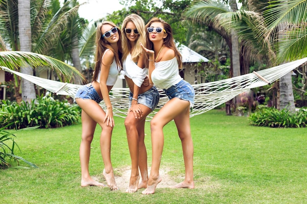 Three amazing stunning fit women with gorgeous long sexy legs posing at tropical garden, wearing trendy mini shorts and simple white tops