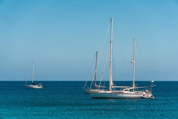 青い海に停泊している3隻のヨット