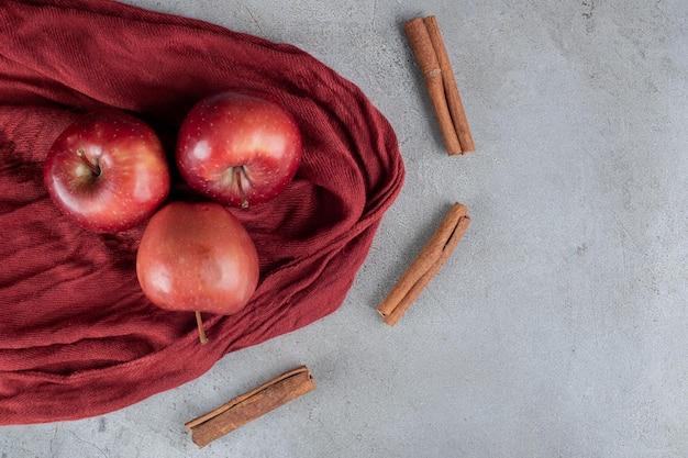 大理石のテーブルにシナモンカットで囲まれた3つのリンゴ。