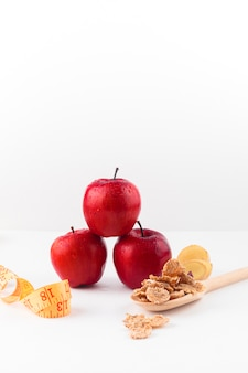 Three apples with measuring tape and cereals on spoon