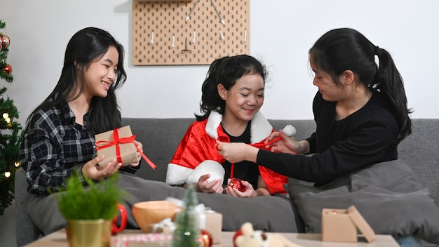 Three asian children opening christmas gift and celebrating christmas together at home.