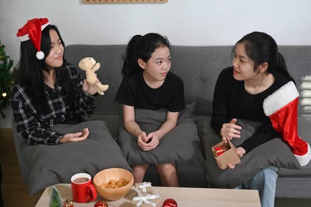 소파에 앉아 집에서 크리스마스를 축하하는 세 명의 아시아 어린이.