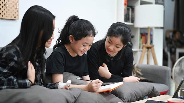Three asian children studying online together in living room.
