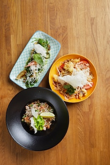 Three asian food dishes on wooden table