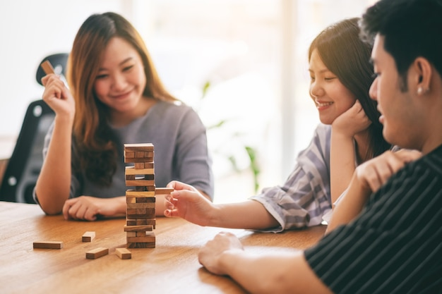 Three asian friends sitting and playing tumble tower wooden block game together with feeling happy