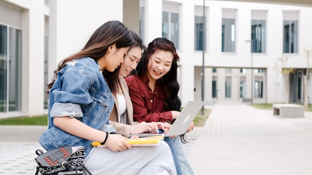 Три азиатских студентки с ноутбуком во время перерыва, сидя в кампусе
