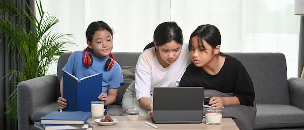 소파에 앉아 집에서 함께 자유 시간을 보내는 세 아시아 여자.