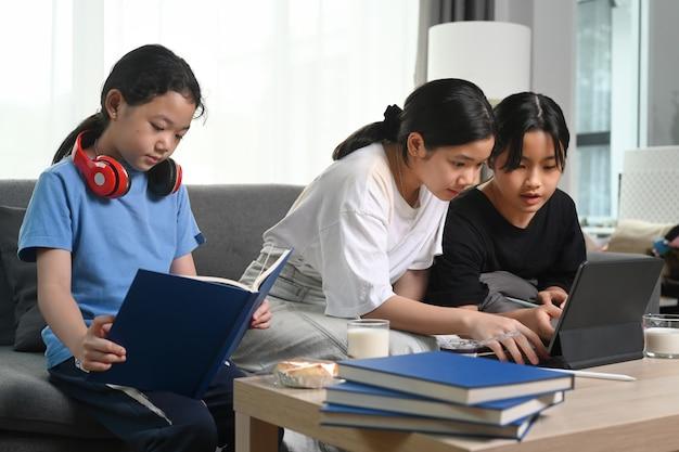 거실에서 소파에 앉아 편안한 집에서 함께 자유 시간을 보내는 세 아시아 소녀.