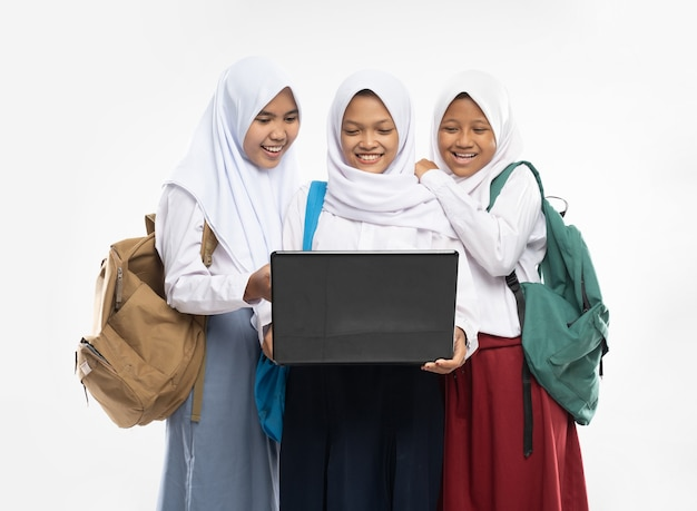 Three asian girls in veils in school uniforms stand smiling using a laptop together while carrying b...