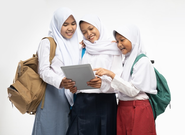 Three asian girls in veils in school uniforms stand smiling using a tablet digital while carrying ba...