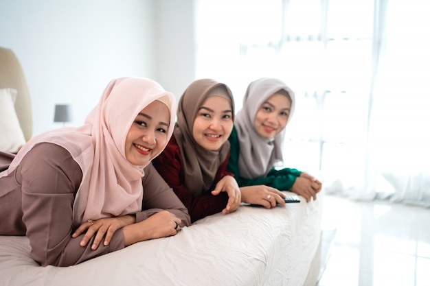 Three asian hijab woman smilling looking at the camera when lying on the bed