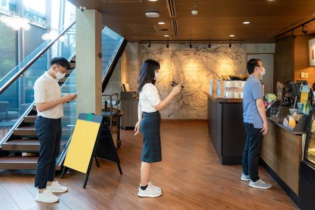 다른 사람들과 6 피트 거리에 마스크를 착용 한 아시아 인 3 명은 covid-19 바이러스와 커피 카페에서 감염 위험에 대해 사회적 거리를 두는 사람들로부터 거리를 유지합니다.