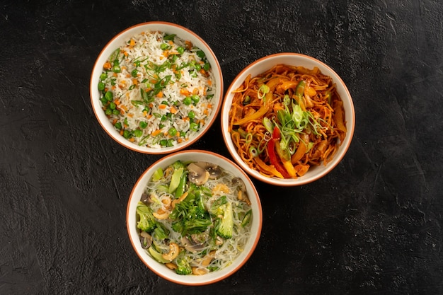 Три азиатских гарнира в круглых тарелках с рисом, яичной лапшой, стеклянной лапшой и овощами.