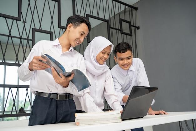 3人のアジアのティーンエイジャーがラップトップと数冊の本を使って制服を着て一緒に勉強します