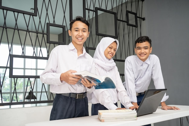 Three asian teenagers studying together in school uniforms smile at the camera while using a laptop ...