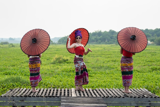 Three asian thai lanna woman in traditional dress hand hold paper umbrella act like model on wooden bamboo bridge with overcast sky .