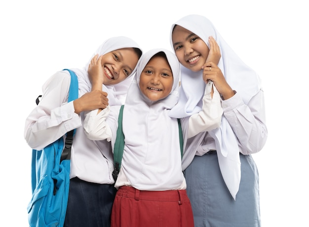 Three asian in veils in school uniforms stand smiling with affectionate gestures of each other while...