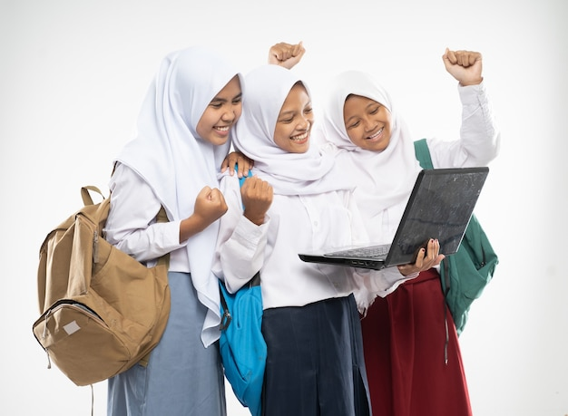 Three asian in veils wearing school uniforms stand using a laptop together with excited gestures and...