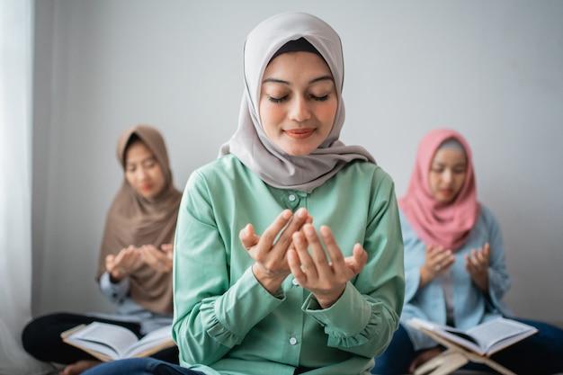 Три азиатские женщины сидят и молятся, чтобы поблагодарить бога