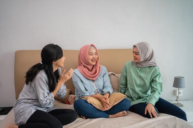 Три азиатские женщины сидят на кровати в чате