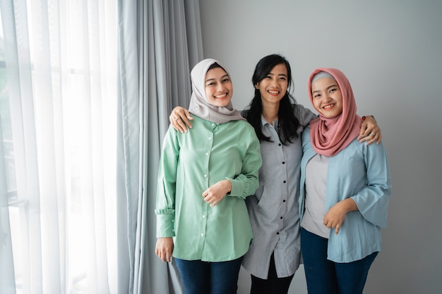 Три азиатские женщины улыбаются стоя рядом друг с другом, собираясь вместе