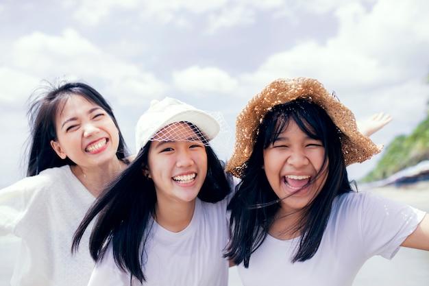 3 아시아 젊은 여자와 바다 해변에서 행복 한 청소년