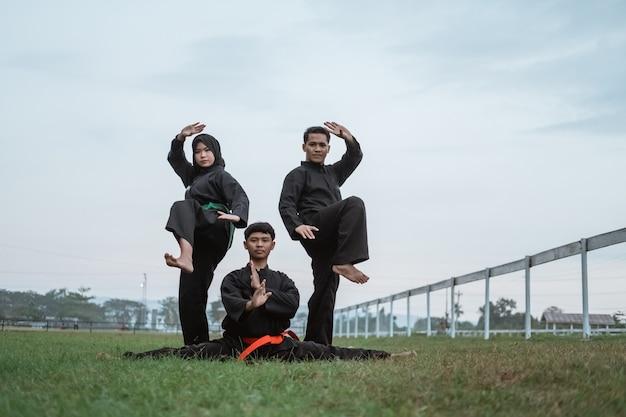 형성과 함께 pencak silat 유니폼을 입고 세 아시아 인