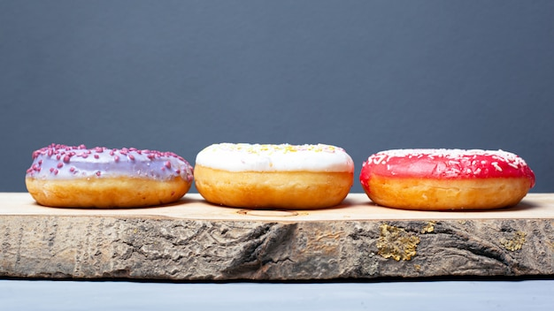 Three assorted glazed donuts of different colors on a wooden plank on a gray background.