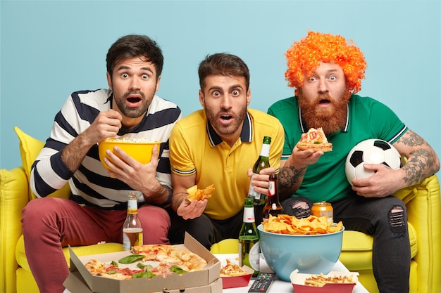 Three astonished male friends stare at camera, eat tasty pizza, popcorn, crisps, drink cold beer